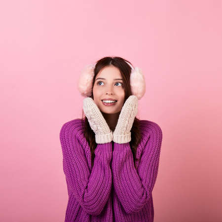 Cute young teenager in a knitted sweater and mittens and fluffy winter pink headphones. The girl smiles gently looks to the side and presses her hands to her face. Photo on pink background.Copy space. Stock Photo