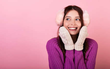 Funny young lady in a knitted sweater and mittens and fluffy winter pink headphones. The girl smiles looks to the side and presses her hands to her face close-up. Photo on pink background. Copy space.