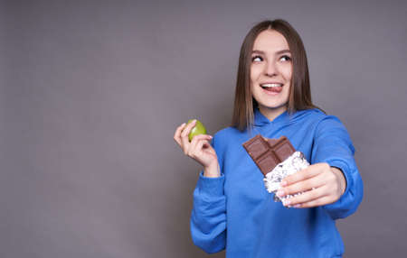 Beautiful funny charming young girl, with long blond hair and brown eyes, dressed in a blue hoodie, chooses what to eat, apple or chocolate. The concept of healthy eating. Copy space.