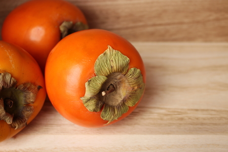 Freshly persimmons fruits in the wooden box over wooden background. With a place for an inscription. Healthy fruit