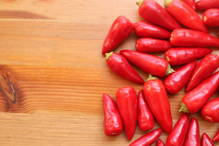 The multitude of red chili on the wooden table with copy space with a blurred background,free place for text.
