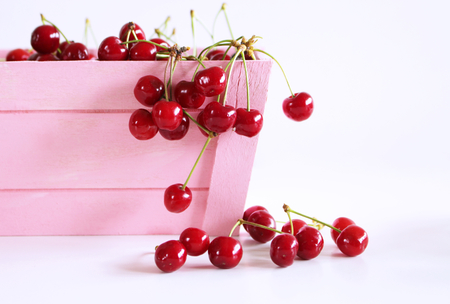 Pink wood box with red fresh cherries on white background. Highly nutritious fruit, often found wild. Cherries close-up. Healthy and colorful concept. Food concept,empty space for your text.