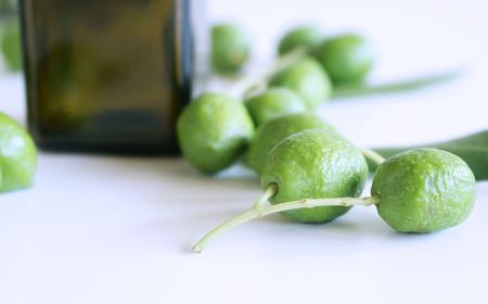 Fresh green olives isolated on white background close up.