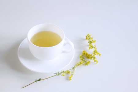 Tea in porcelain mug on white background with galum verum, ladys bedstraw or yellow bedstraw. Galum verum is a herbaceous perennial plant. When used externally, this tea treats all skin diseases .