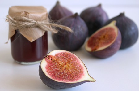 Glass jar of fig jam and fresh figs on white wooden table, side view. Close-up. Archivio Fotografico