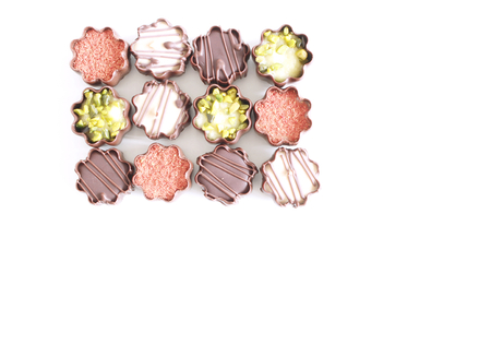 Top view of various chocolate pralines isolated on white background.Exclusive chocolate candies, product concept for chocolatier.