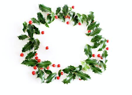 Christmas holly Ilex aquifolium isolated on white table background. Evergreen leaves with red berries. Decorative floral frame, web banner. Flat lay, top view,empty space for holiday text.