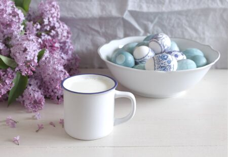 Spring breakfast still life scene. White mug with milk, Easter eggs on a porcelain white bowl and beautiful purple lilac .Easter food and drink concept. Farmhouse table composition.