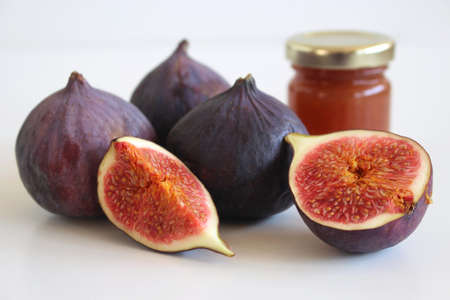Fresh ripened purple figs. Creative composition a decorative banner of whole and sliced exotic fruit and fig jam isolated on white table background.Food photography. Nature concept.
