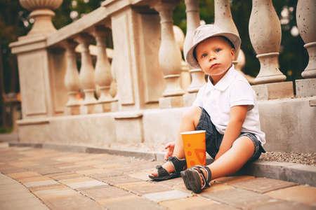balustrade: boy sitting on sett near balustrade