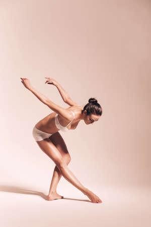 bending down: bailarina agacharse en el estudio caliente