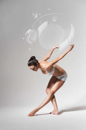 ballerina bending down with soap bubbles Stock Photo