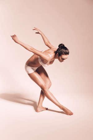 bending down: bailarina gr�cil agach�ndose para la pierna Foto de archivo