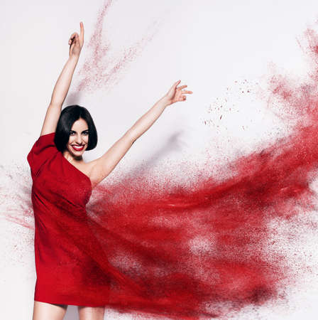 dancing brunette woman in red powder Stock Photo