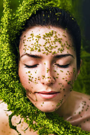 healthy sensual woman with plant on face photo