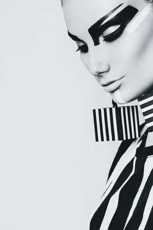 top model: portrait of creative woman with striped earrings in studio