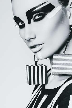 mujer sexy: Retrato de mujer con aretes cubo rayas en estudio Foto de archivo