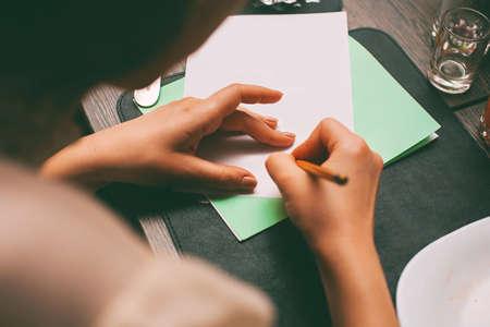 papier a lettre: femme �crivant contrat dans le caf� Banque d'images