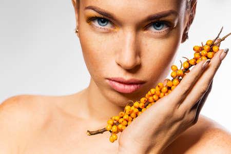 argousier: belle femme tenant la branche de l'argousier