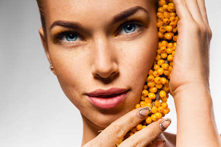 seabuckthorn: close up portrait of woman with sea-buckthorn