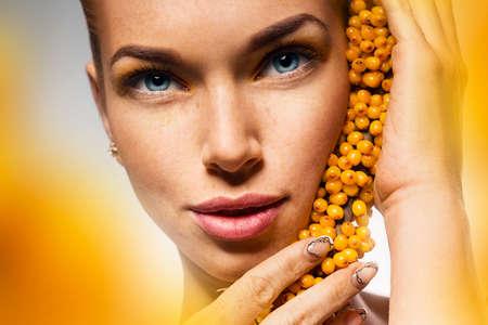 argousier: fermer up portrait d'une femme avec du jaune d'argousier
