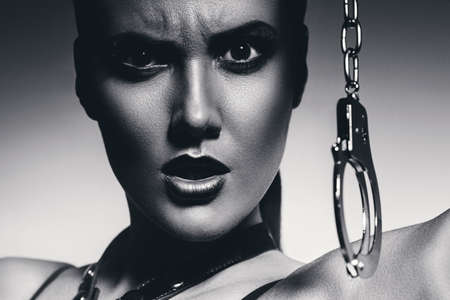 bdsm handcuff: black and white angry woman with handcuffs
