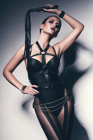 hot woman in black corset with whip Stock Photo