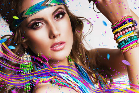 beautiful woman with multi necklace and colourful lines in studio