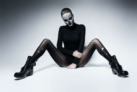 torn stockings: dark woman with skull face on the floor