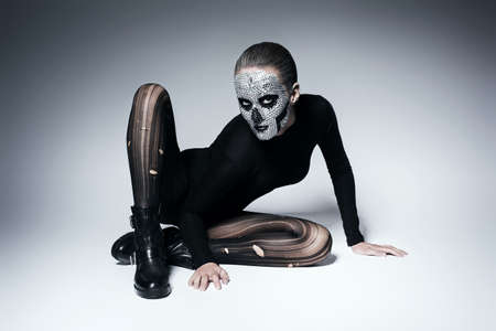 torn stockings: scary fashionable woman posing on the floor
