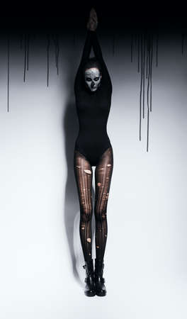 torn stockings: woman in skull make-up and paint Stock Photo