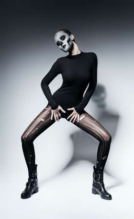 torn stockings: woman with skull posing in black clothing Stock Photo