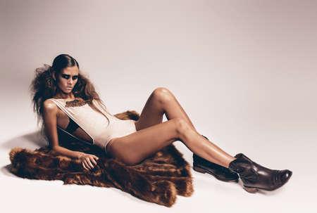 manteau de fourrure: femme sexy se trouve sur manteau de fourrure en bottes