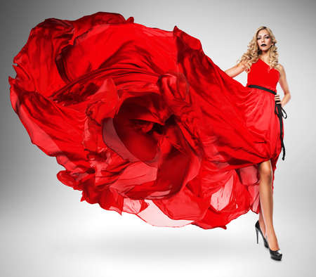wind blown hair: blond woman in beautiful red dress