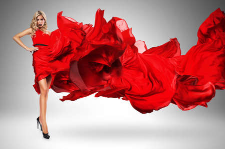 wind blown hair: blond woman in beautiful blown red dress Stock Photo