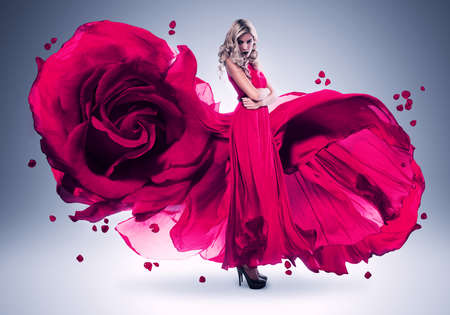 wind blown hair: blond woman in long pink rose dress Stock Photo