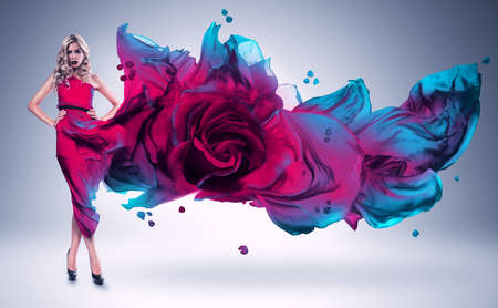 wind blown hair: blond woman in pink and blue rose dress Stock Photo