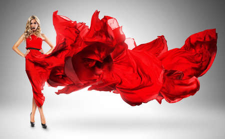 wind blown hair: blond woman in windy red dress Stock Photo