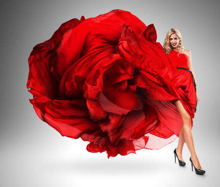 wind blown hair: smiling woman in large red dress Stock Photo