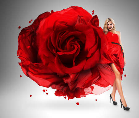 wind blown hair: smiling woman in large red rose dress Stock Photo