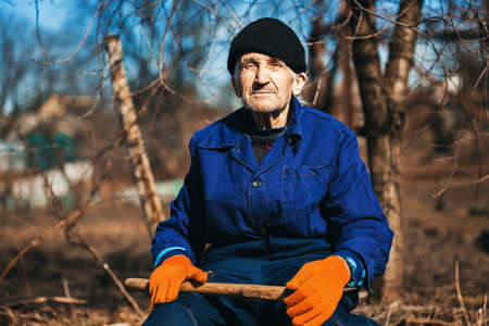 workwear: old man in workwear sitting outdoors with axe outdoors Stock Photo