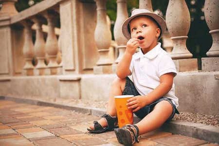 balustrade: boy in hat sitting near balustrade