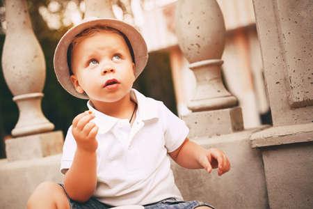balustrade: cute little boy in hat near balustrade Stock Photo