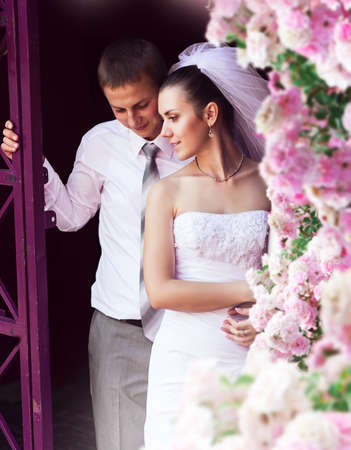 wedding couple: bride and groom near pink roses