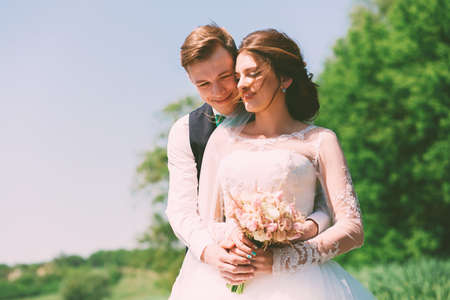 bride dress: bride and groom smiling on nature Stock Photo