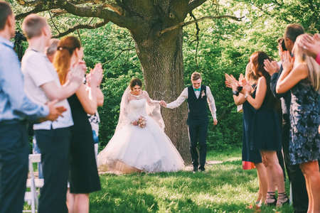 guests: bride and groom running between guests lines Stock Photo