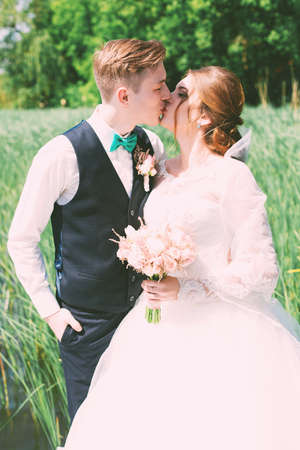 bride kissing groom in tall grass photo