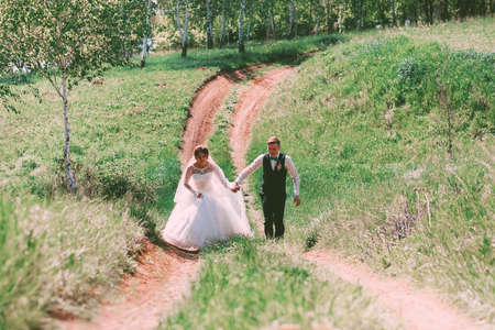 happy bride and groom running on road photo