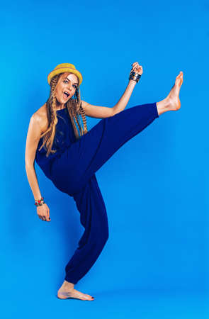 blue overall: funny dancing blond woman in blue overall on blue background Stock Photo