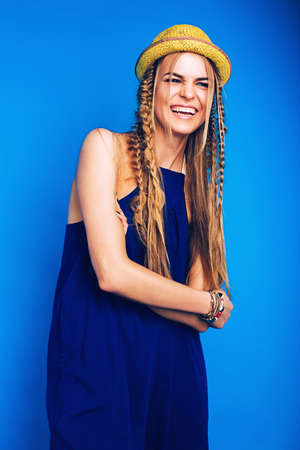ultramarine blue: happy laughing woman in blue overall and yellow hat on blue background